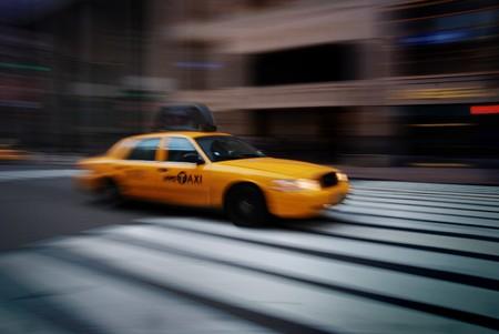 New York City yellow cab speeding on street crossing sidewalk.