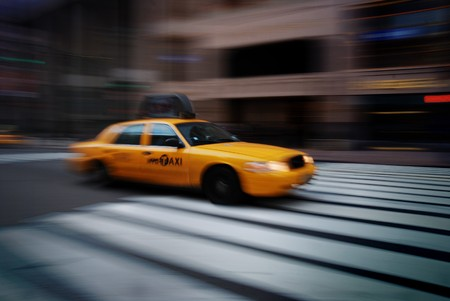 a yellow taxi: New York City yellow cab speeding on street crossing sidewalk.