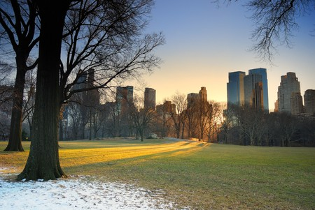 city park skyline: Central Park, New York City, with skyscrapers,snow and sunset Stock Photo