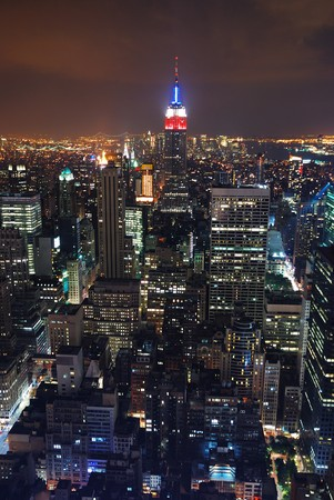 Aerial view of New York City at night with Empire State building in the center.