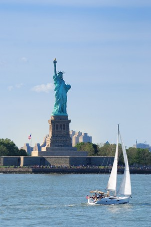 Statue of Liberty as American landmark in New York City Manhattan over Hudson River with sailing boat  photo