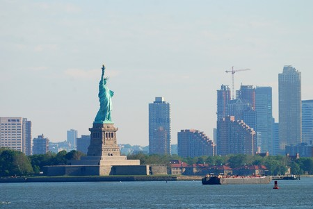 financial freedom: New York City Statue of Liberty with skyscrapers in Manhattan Stock Photo