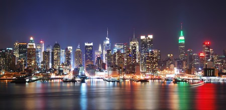 scrapers: New York City night skyline panorama over Hudson river with boat and skyscraper and colorful reflections.