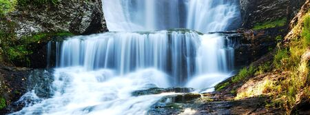Waterfall panorama in Autumn with rocks and foliage photo