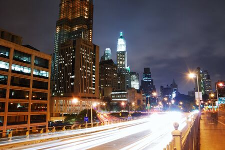 Manhattan street view at night in New York City with light beams of traffic on road.