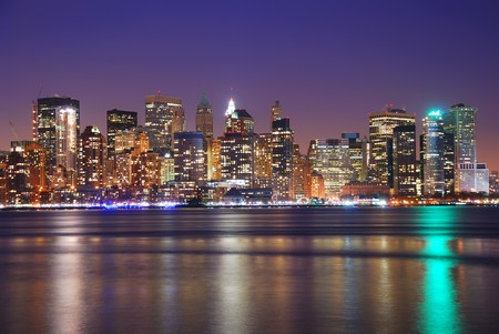 times: New York City Downtown at night over Hudson River with reflections.