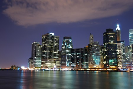 New York City Manhattan skyline with office skyscrapers building in at dusk illuminated with lights at night over Hudson River