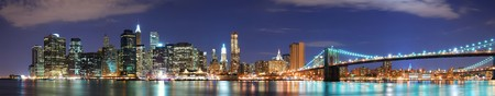 New York City Manhattan skyline panorama with Brooklyn Bridge and office skyscrapers building in at dusk illuminated with lights at night