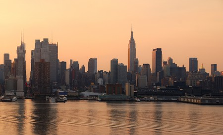Manhattan urban skyline panorama in New York City with Empire State Building at sunrise over Hudson River photo