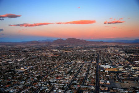 stratosphere: Modern city with mountain at sunset. Las Vegas aerial view at sunset with mountain and luxury hotels.