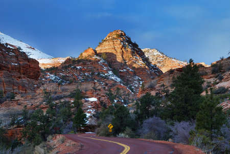 Zion National Park in the morning with red rocks, road and snow in winter, Utah.