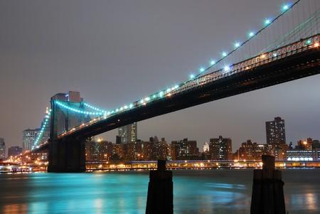 Brooklyn bridge at night with New York City skyline over Hudson River.  photo