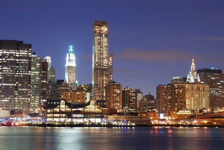 lower manhattan: New York City Manhattan skyline with office skyscrapers building in at dusk illuminated with lights at night over Hudson River