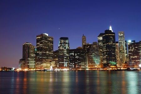hudson river: New York City Manhattan urban skyline over Hudson River with office skyscrapers building in at dusk illuminated with lights at night