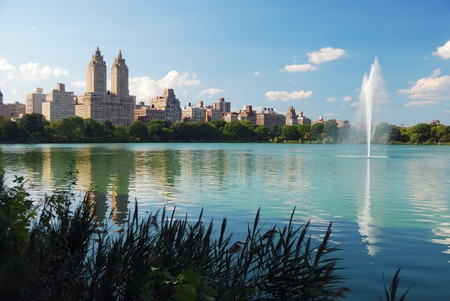 New York City Central Park fountain and urban Manhattan skyline with skyscrapers and trees lake reflection with blue sky and white cloud.