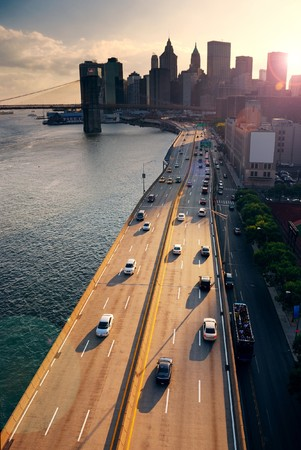 Busy traffic in New York City Manhattan with Brooklyn Bridge across Hudson River at sunset.