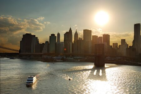 New York City Manhattan sunset with Brooklyn bridge and boat in Hudson River. photo