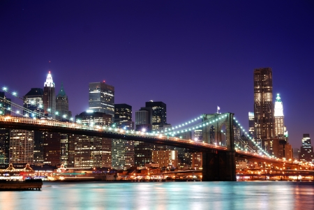 New York City Brooklyn Bridge and Manhattan skyline with skyscrapers over Hudson River illuminated with lights at dusk after sunset. Stok Fotoğraf
