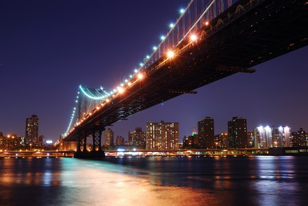 New York City-Manhattan Bridge über Hudson River mit Skyline nach Sonnenuntergang Nacht von Sicht beleuchtet mit Lichtern aus Brooklyn angezeigt.