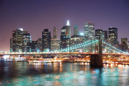 New York City Brooklyn Bridge and Manhattan skyline with skyscrapers over Hudson River illuminated with lights at dusk after sunset. Stock Photo