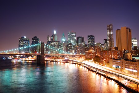 New York City Manhattan skyline and Brooklyn Bridge with skyscrapers over Hudson River illuminated with lights and busy traffic at dusk after sunset. photo