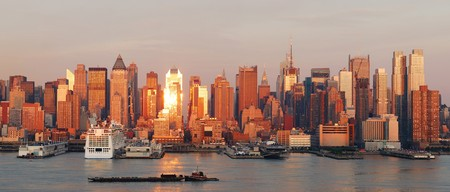 New York City Manhattan skyline panorama at sunset with skyscrapers and sunshine reflection over Hudson river. photo