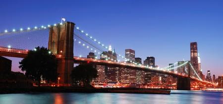 ニューヨーク市ブルックリン橋とマンハッタンのスカイラインのパノラマ夕暮れ日没後のライトで照らされたハドソン川の上の高層ビルを表示しま