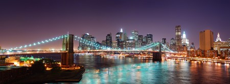New York City Brooklyn Bridge and Manhattan skyline panorama view with skyscrapers over Hudson River illuminated with lights at dusk after sunset. photo