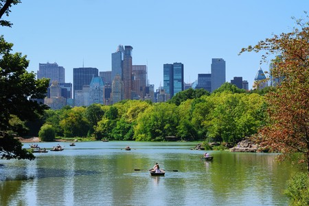 central: Central Park de Nueva York con los rascacielos de Manhattan skyline y cielo azul con barco en el lago.  Foto de archivo