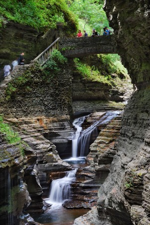 Waterfall with bridge and hiking trail in woods with rocks and stream in Watkins Glen state park in New York State photo