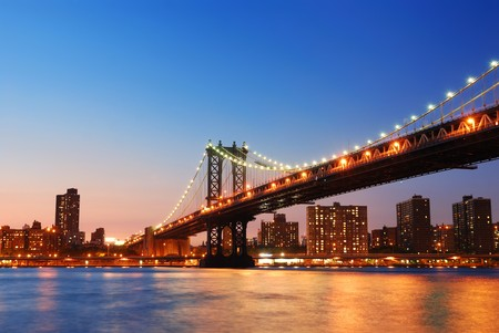 New York City Manhattan Bridge over Hudson River with skyline after sunset night view illuminated with lights viewed from Brooklyn. photo