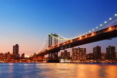 New York City Manhattan pont sur la rivière Hudson avec skyline après que la nuit du coucher du soleil avis éclairé avec lumières vu de Brooklyn.