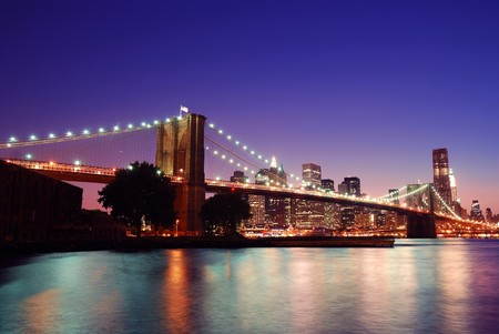 New York City Brooklyn Bridge and Manhattan skyline with skyscrapers over Hudson River illuminated with lights at dusk after sunset. photo