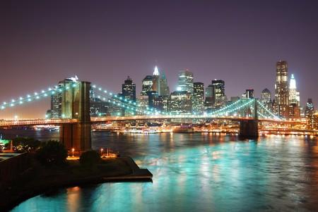 lower manhattan: New York City Manhattan skyline and Brooklyn Bridge at dusk over Hudson River with skyscrapers