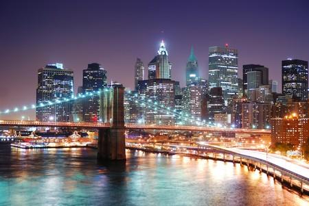 New York City-Manhattan Skyline und Brooklyn Bridge mit Wolkenkratzern über Hudson River bei Dämmerung nach Sonnenuntergang mit Lichtern und busy Traffic beleuchtet.