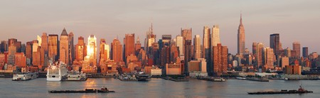 pano: New York City Manhattan skyline panorama at sunset with empire state building and skyscrapers with reflection over Hudson river. Stock Photo