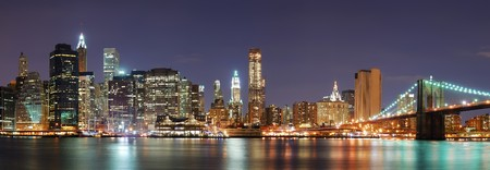 New York City Manhattan skyline panorama with Brooklyn Bridge and office skyscrapers building in at dusk illuminated with lights at night photo