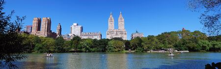 New York City Central Park panorama with Manhattan skyline skyscrapers and blue sky with boat in lake. photo