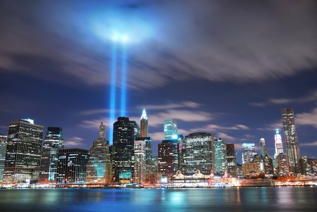 nyc skyline:  New York City Manhattan panorama view at night with office building skyscrapers skyline illuminated over Hudson River and two light beam in memory of September 11.