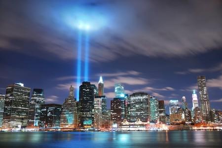skyline nyc: Panorama de la ciudad de Nueva York Manhattan ver por la noche con la silueta de rascacielos iluminado sobre el r�o Hudson y dos haz de luz en la memoria del 11 de septiembre de edificio de oficinas.