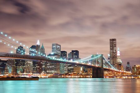 New York City Manhattan panorama view with Brooklyn Bridge at night with office building skyscrapers skyline illuminated over Hudson Rive photo