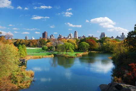 city park skyline: New York City Central Park in Autumn with Manhattan skyscrapers and colorful trees over lake with reflection.