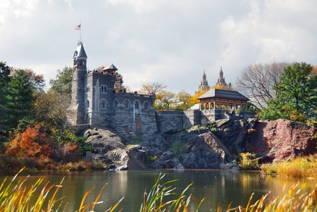city park skyline: New York City Manhattan Central Park in Autumn with Belvedere Castle and colorful trees over lake with reflection.