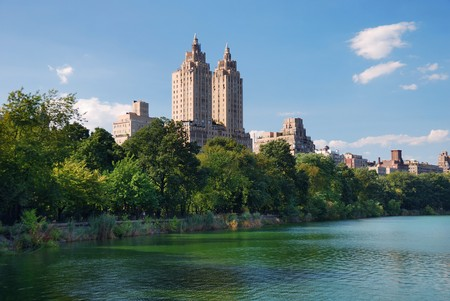 New York City Central Park urban Manhattan skyline with skyscrapers and trees lake reflection with blue sky and white cloud. photo