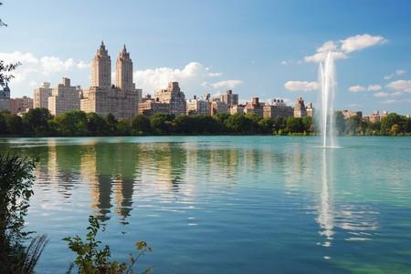 ニューヨーク市中央公園の噴水と青い空と白い雲の高層ビルや木湖の反射との都市マンハッタンのスカイライン。