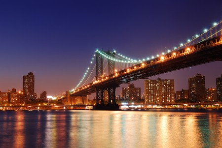 city lights: New York City Manhattan Bridge over Hudson River with skyline after sunset night view illuminated with lights viewed from Brooklyn.
