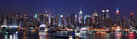夜にハドソン川にニュージャージーから見た同胞ニューヨーク市マンハッタンのスカイラインのパノラマ