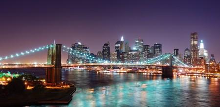 Pont de Brooklyn de New York City et de Manhattan skyline panorama vue avec les gratte-ciels au-dessus de la rivière Hudson, illuminée par les lumières au crépuscule après le coucher du soleil. Banque d'images