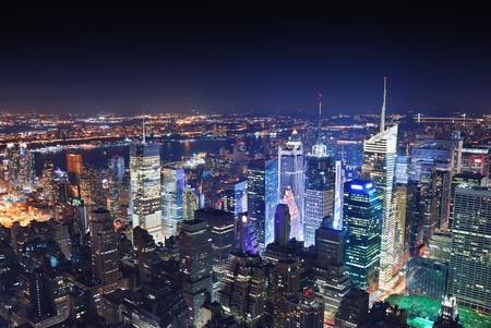 midtown: New York City Manhattan Times Square panorama aerial view at night with office building skyscrapers skyline illuminated by Hudson River. Stock Photo