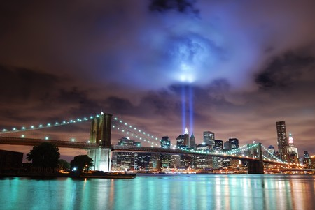 Remember September 11. New York City Manhattan panorama view with Brooklyn Bridge at night with office building skyscrapers skyline illuminated over Hudson River and two light beam in memory of September 11. Stock Photo